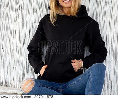 Unrecognizable woman sits in front of camera, she wears black hoodie. There is a place on hoodie for inscription or design for fashion mockup. Casual outfit for lady.