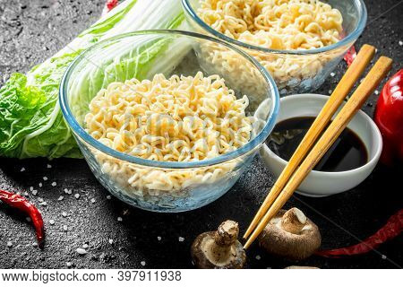Instant Noodles In Bowls With Mushrooms, Peking Cabbage And Soy Sauce. On Black Rustic Background