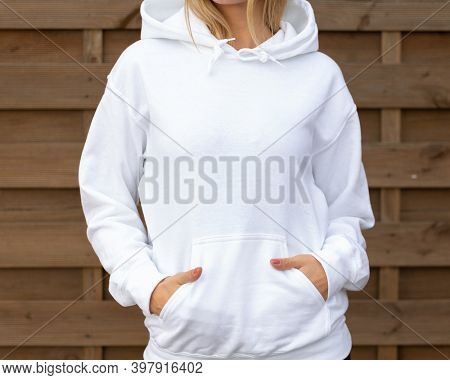 Woman is standing in white hoodie with hands in pockets in front of camera. She is posing for clothing mockup. On her hoodie is empty space for design or incription.