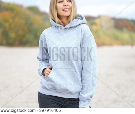 Blond woman is standing on the beach. She is wearing light grey hoodie. On her blouse is empty area for design or inscription. Fashion mockup with casual outfit.