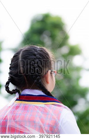 Vertical Photos. Braided Girl Stood Back And Looked To The Front. Children Wearing Graduation Gowns