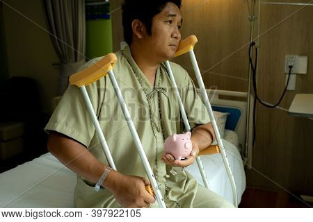 A Man's Holding A Piggy Bank And Crutches Sitting On Bed After Surgery Recovery Injury Broken Bones