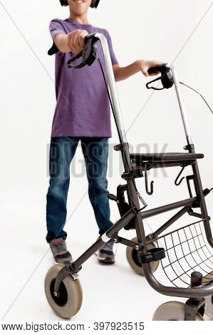 Cropped Shot Of Teenaged Disabled Boy With Cerebral Palsy Taking Steps With His Walker Isolated Over