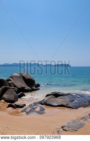 Sandy Beach With Huge Stones Against The Blue Sea On A Sunny Day In Thailand