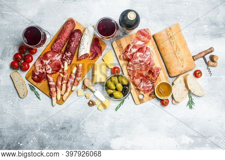 Antipasto Background. Different Italian Snacks With Red Wine. On A Rustic Background.
