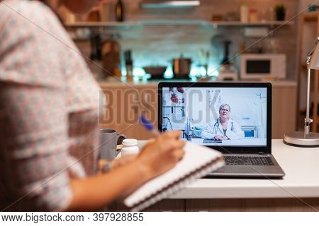 Doctor Explaining Diagnosis During A Video Conference With Patient At Midnight. Physician Giving Con