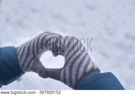 Women's Hands In Mittens Show A Heart On A Background Of Snow, Wintertime.
