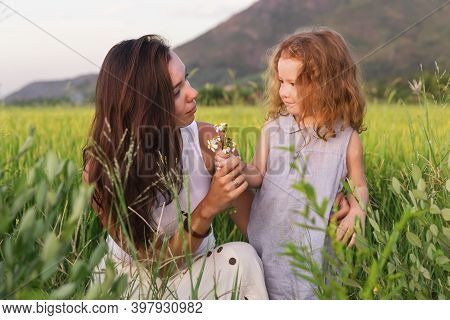 Young Mother And Daugther Look On The Flower Near Rice Field, Nature, Travel