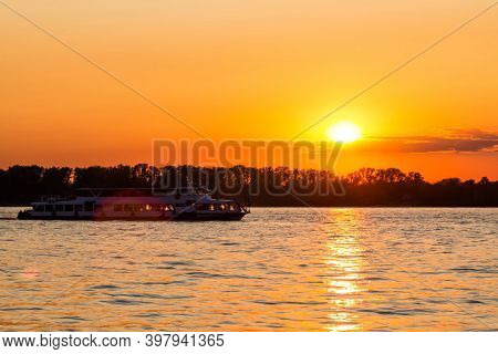 A Small Excursion Riverboat Floats On The River Against The Backdrop Of A Picturesque Sunset