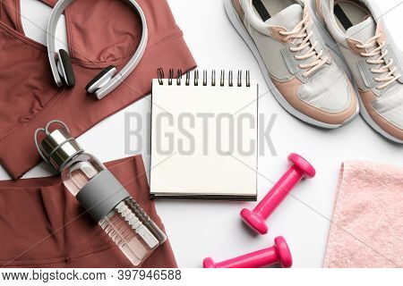 Flat Lay Composition With Sportswear, Notebook And Dumbbells On White Background. Gym Workout Plan