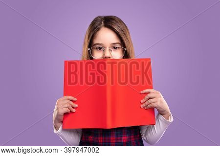 Smart Diligent Little Schoolgirl In Glasses And Checkered Dress Holding Open Red Book And Looking At