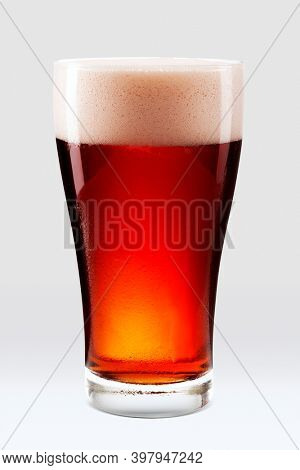 Fresh amber beer with foam in a pint