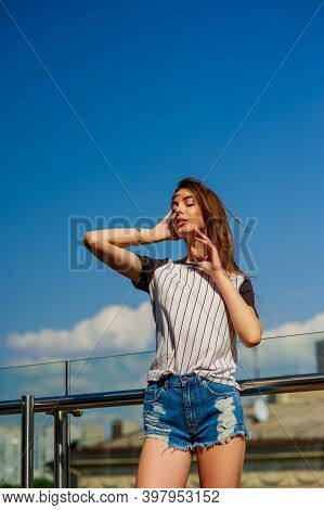 Girl In Denim Shorts On The Balcony. Mini Denim Shorts. Woman In A Striped Shirt.