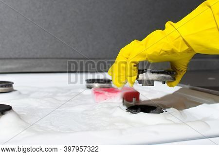 Female Hand In Glove Lifting The Burner Of Gas Stove. Housewife Cleaning Gas Stove With Sponge And C