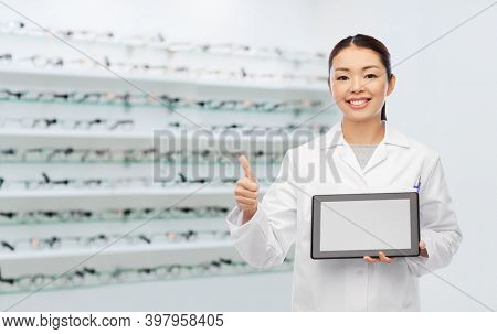medicine, vision and healthcare concept - happy smiling asian female eye doctor or ophthalmologist with tablet pc computer showing thumbs up over glasses at optical store background