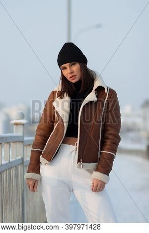 Alluring Woman Wearing Brown Sheepskin Jacket With Hat And Looking At Camera Standing On Snowy City