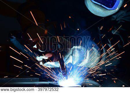 Employee Welding Steel With Sparks Using Mig Mag Welder - Focus On Sparks. Welder Welding Metal