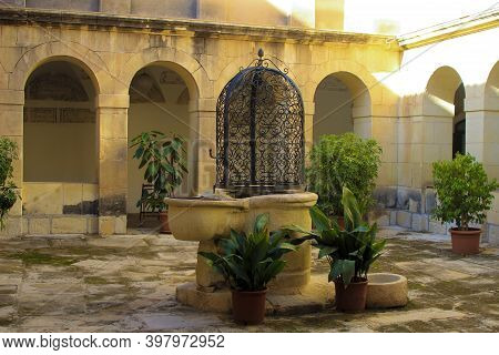 Elche, Alicante, Spain- November 30, 2020: Beautiful Cloister With Well With Wrought Iron Details In