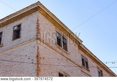 Bottom Side View On Damaged Facade Of Building With Bricks And Broken Windows, Exterior Of An Old Bu