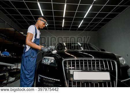 Car Detailing Series. Polishing Of Luxury Black Car At Professional Auto Service Station. Young Afri