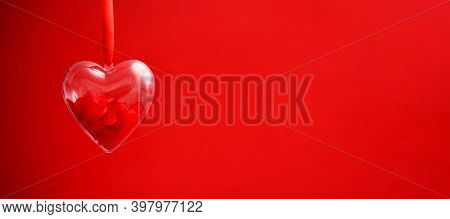 Transparent Heart With Red Confetti Inside On Red Background. Valentines Day Greeting Card Concept.