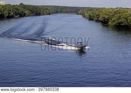 Speedboat Towing An Athlete On A Board Against The Background Of The Forest. Athlete Water Skiing An