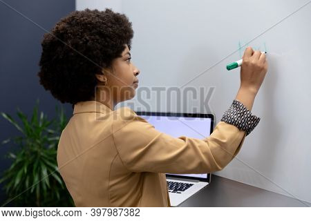 Mixed race businesswoman writing on whiteboard in creative office. social distancing in business office workplace during covid 19 coronavirus pandemic.