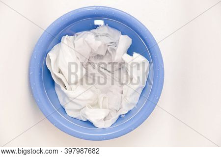 Laundry Concept With Soak White Clothes In Blue Bowl Prepared For Hand Washing With Copy Space On Wh