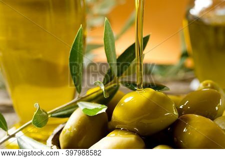 Green Olives And Olive Oil On A Wood Background. Different Types Of Olives, Olive Oil And Olive Leav