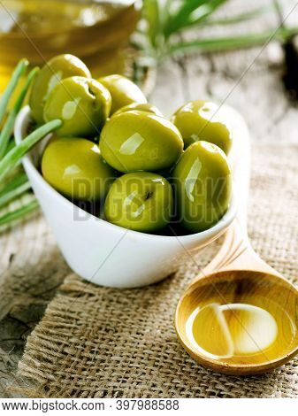 Green Olives And Olive Oil On A Wood Background. Different Types Of Olives And Olive Leaves.