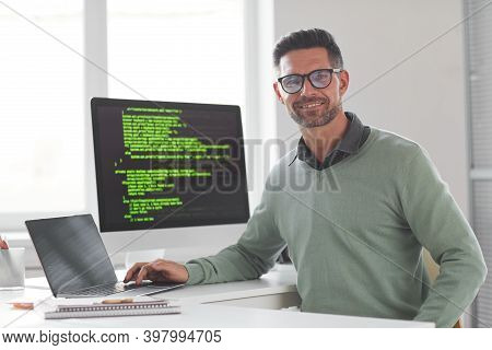 Portrait Of Mature Computer Programmer In Eyeglasses Looking At Camera While Developing New Computer