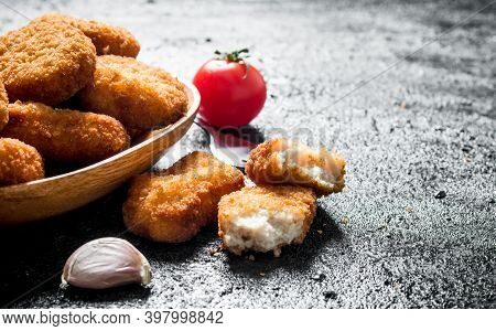 Chicken Nuggets In A Bowl And Pieces Of Nuggets. On Black Rustic Background