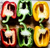 picture of cross sections of red, green and yellow bell peppers poster