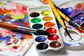 Art palette, watercolors,  paintbrushes on the table poster