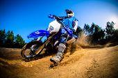 Enduro bike rider on action. Turn on sand terrain. poster