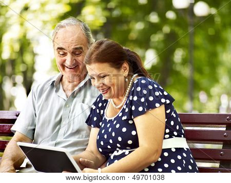 Old couple with tablet pc sit on bench  . Outdoor.