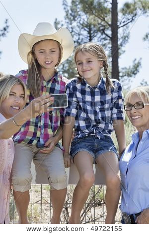 Happy family taking self portrait through cell phone outdoors