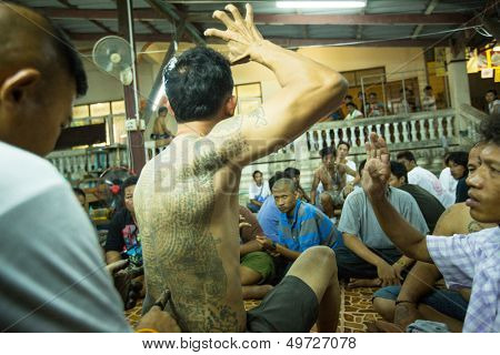 NAKHON CHAI, THAILAND - MAR 23: Unidentified monk makes traditional Yantra tattooing during Wai Kroo Master Day Ceremony in Wat Bang Pra on Mar 23, 2013 in Nakhon Chai, Thailand.