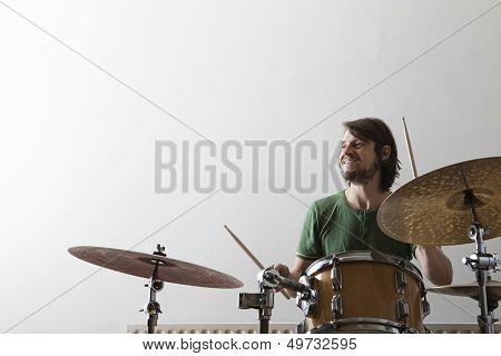 Smiling young man playing drum set
