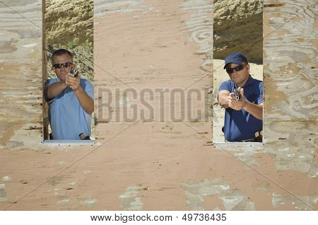 Two men aiming hand guns at firing range