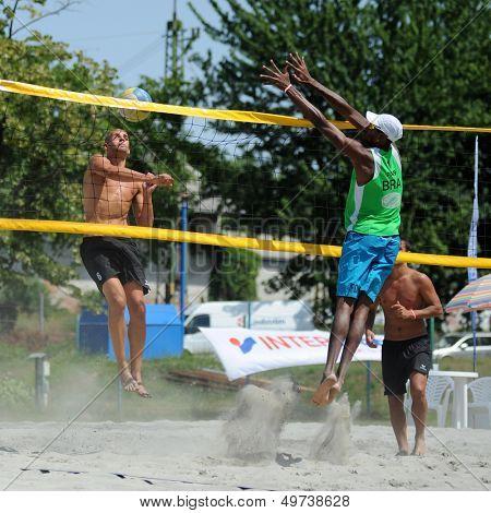KAPOSVAR, HUNGARY - AUGUST 4: Leonel Munder (in green) in action at a ROAK Viragfurdo Kupa beach volleyball competition, August 4, 2013 in Kaposvar, Hungary.