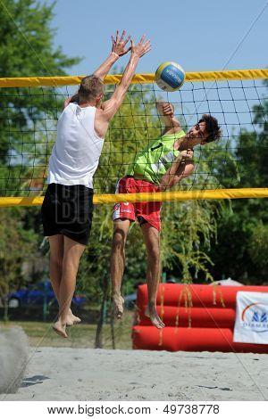 KAPOSVAR, HUNGARY - AUGUST 4: Bence Bozoki (in white) in action at a ROAK Viragfurdo Kupa beach volleyball competition, August 4, 2013 in Kaposvar, Hungary.