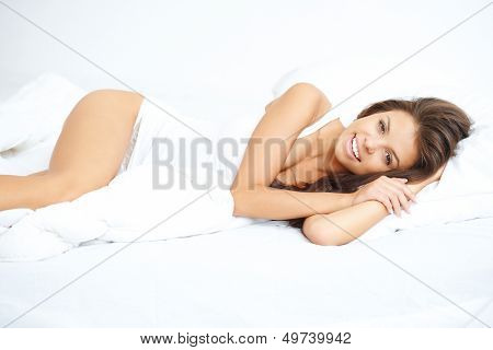 Vivacious young woman in bed lying in bedclothes giving the camera a beautiful smile