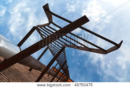 Broken Old Fire Escape Metal Stairs Above Blue Cloudy Sky