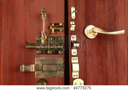 Metal bolts, latches and hooks in wooden open door close-up