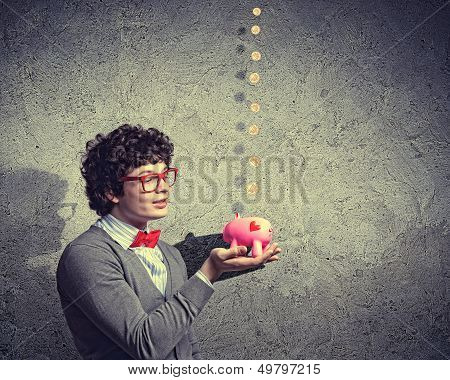 Image of young businessman in red glasses holding moneybox poster