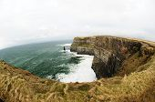 The Cliffs of Moher (Irish: Aillte an Mhothair) are located at the southwestern edge of the Burren region in County Clare Ireland. They rise 120 metres (390 ft) above the Atlantic Ocean at Hag's Head and reach their maximum height of 214 metres (702  poster