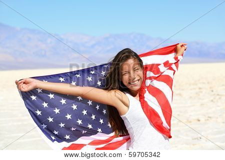 Beautiful patriotic vivacious young woman with the American flag held in her outstretched hands standing in the summer sunshine in front of an expanse of white sand and distant mountains