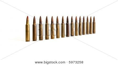 Row of standing M16 cartridges converging in perspective isolated