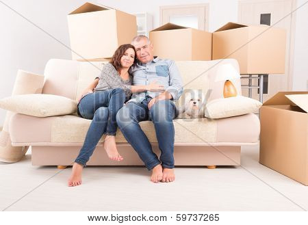 Happy mature couple celebrating their new home sitting together on the sofa with their little dog  just after moving in